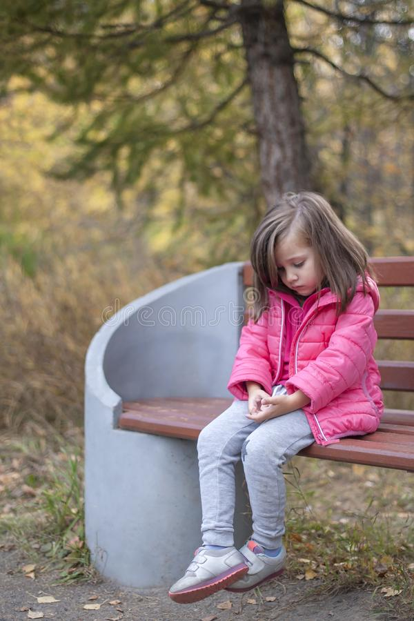 Trauriges kleines Mädchen, das auf Bank im Park sitzt lizenzfreie stockfotografie