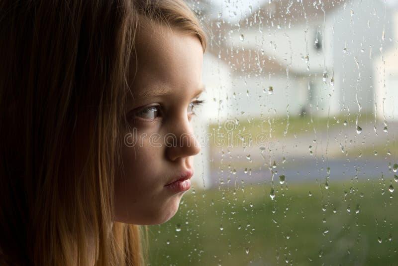 Trauriges kleines Mädchen, das heraus regnerisches Fenster anstarrt stockfotografie