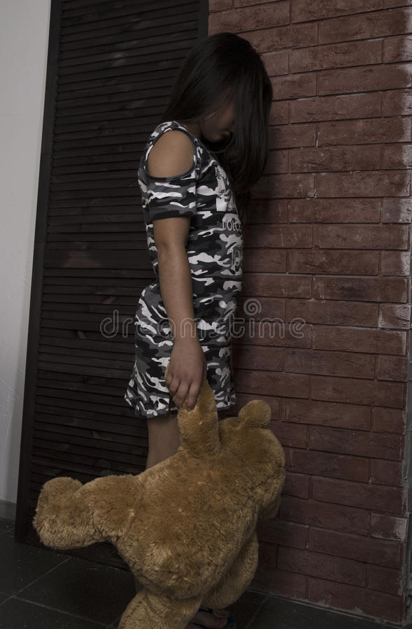 Trauriges kleines Mädchen, das ihren Teddybären umfasst bestraftes Mädchen, das nahe Backsteinmauer steht stockfoto