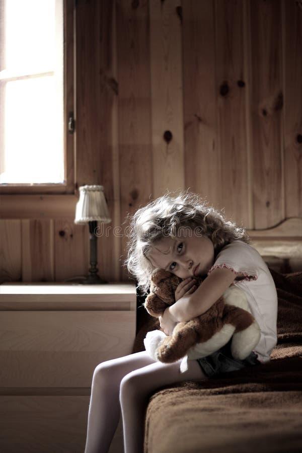 Trauriges kleines Mädchen, das Teddybären umarmt stockfotografie