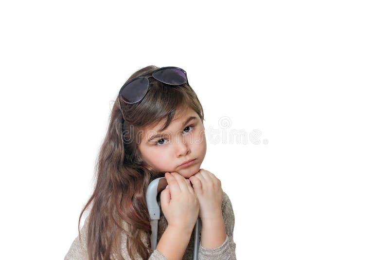 Trauriges kleines Mädchen lehnt sich auf dem Griff eines Koffers und des looki stockfotografie