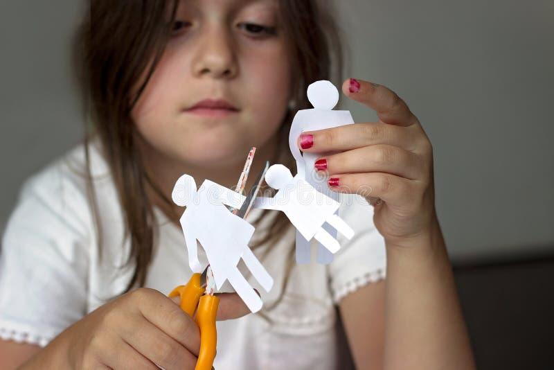 Trauriges kleines Mädchen mit Papierfamilie und Scheren; Scheidung oder famil stockfoto