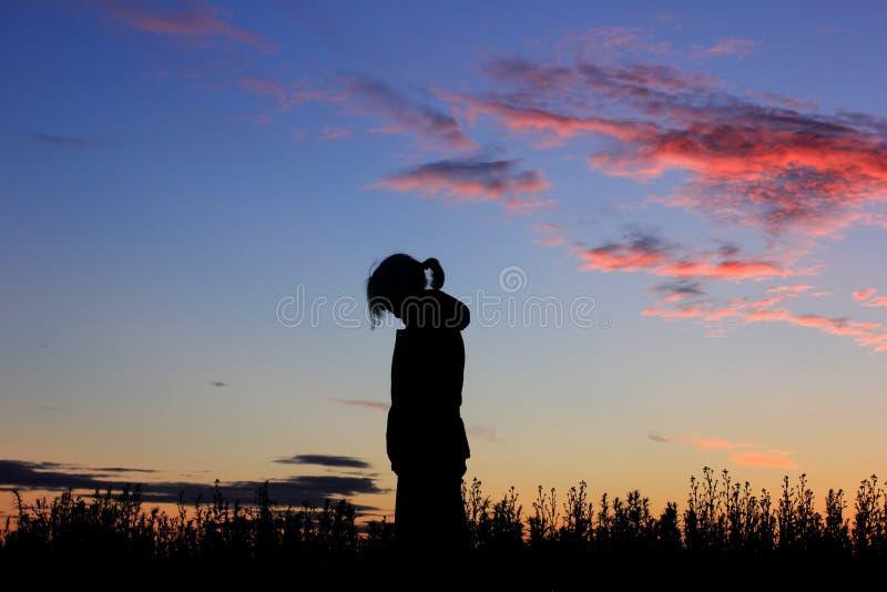 Trauriges Mädchen auf Sonnenunterganghintergrund, Schattenbild lizenzfreies stockfoto