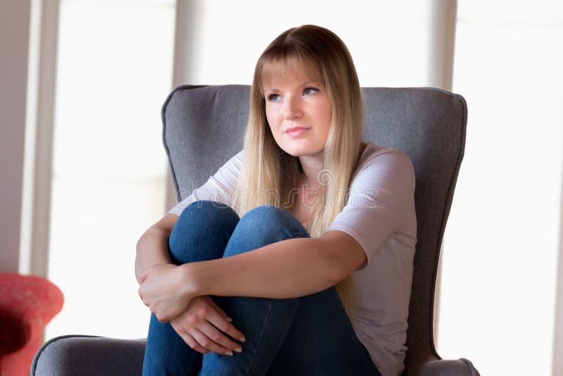 Trauriges Mädchen, das auf Stuhl sitzt stockbild