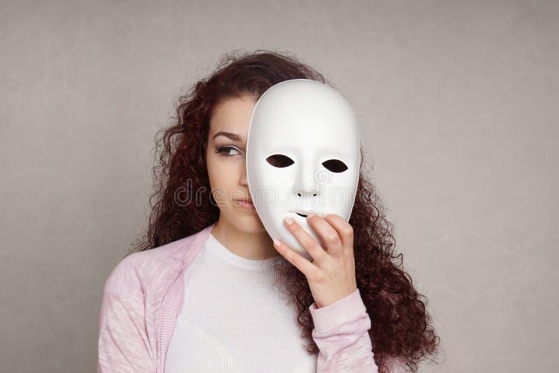 Trauriges Mädchen, das hinter Maske sich versteckt stockfotos