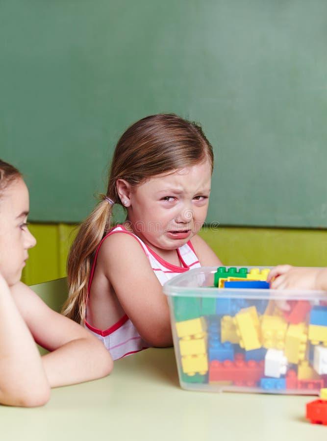 Trauriges Mädchen, das im Kindergarten schreit lizenzfreie stockbilder