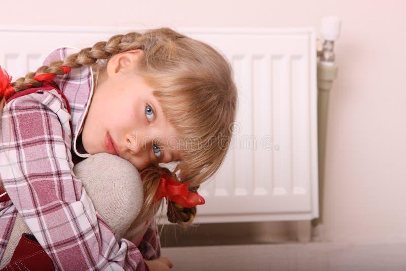 Trauriges Mädchen, das nahe Heizung sitzt. Kindproblem. stockfotografie