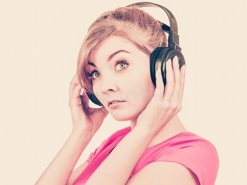 Trauriges Mädchen der Frau in hörender Musik der großen Kopfhörer lizenzfreie stockbilder