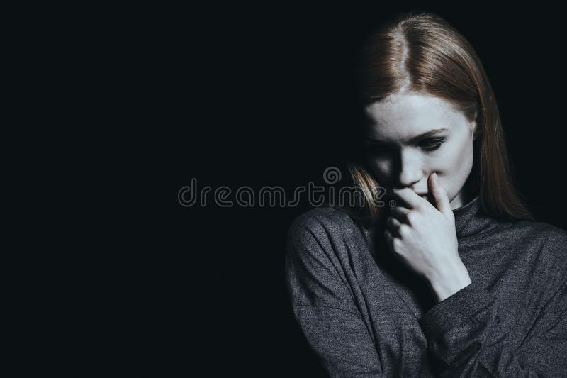 Trauriges Mädchen gegen schwarze Wand stockbild
