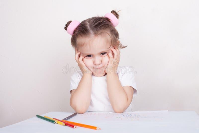 Trauriges Mädchen mit farbigen Bleistiften stockfotografie