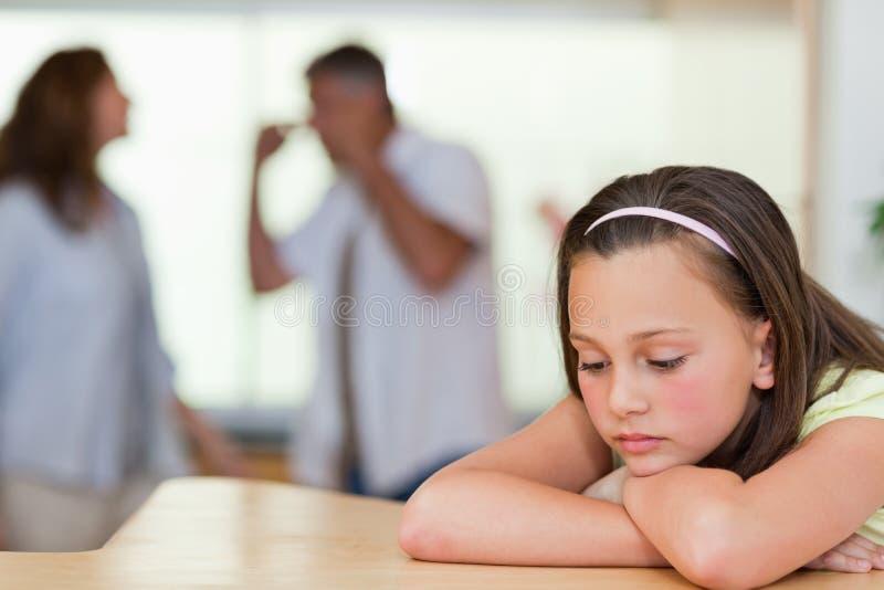 Trauriges Mädchen mit ihrem Kämpfen parents hinter ihr lizenzfreies stockbild