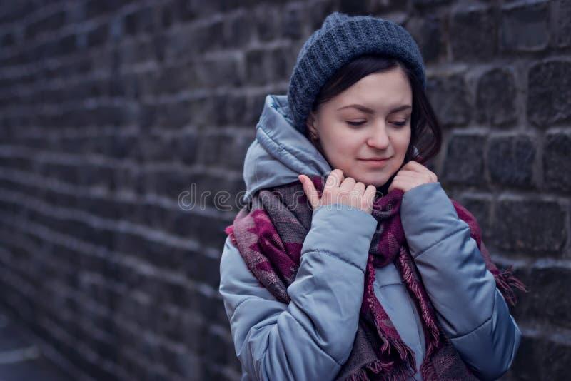 Trauriges Mädchen steht nahe einer Backsteinmauer im Jackenhut und -schal lizenzfreies stockbild