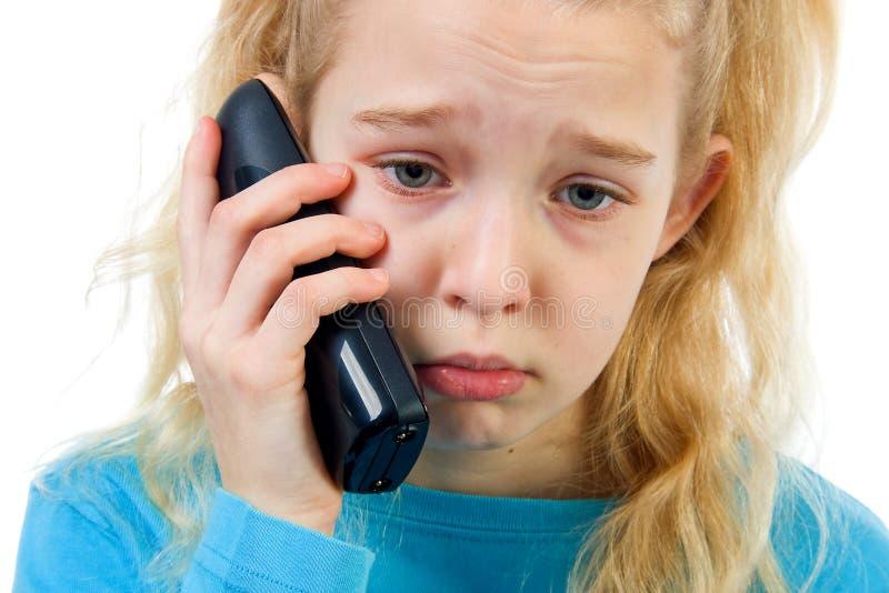 Trauriges Mädchen am Telefon lizenzfreies stockbild