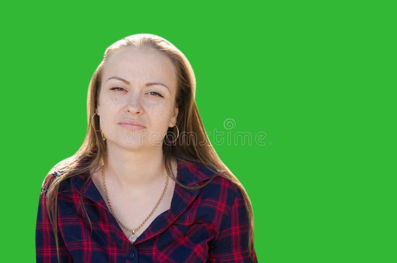Trauriges schönes Mädchen mit langen Haarblicken direkt auf die Kamera lokalisiert auf grünem Hintergrund lizenzfreies stockfoto