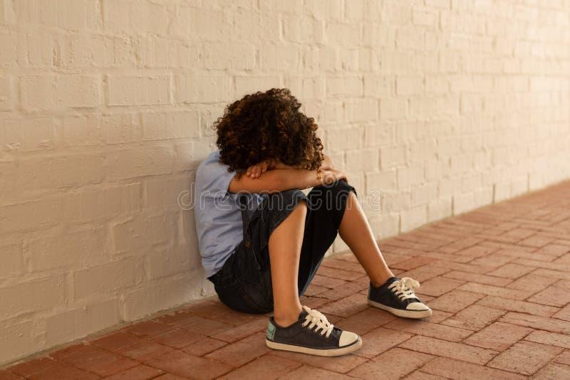 Trauriges Schulmädchen, das allein auf Boden im Korridor sitzt lizenzfreies stockbild