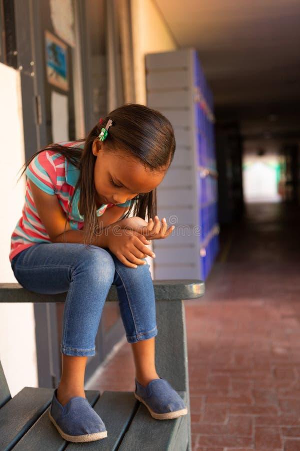 Trauriges Schulmädchen, das allein auf der Bank im Korridor sitzt lizenzfreies stockbild