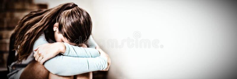 Trauriges Schulmädchen, das allein auf Treppenhaus sitzt stockfotografie
