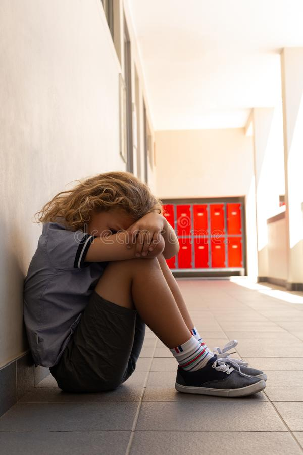 Trauriges Schulmädchen, das auf dem Boden mit seinem Kopf unten sitzt lizenzfreies stockfoto