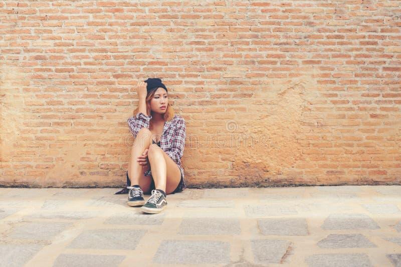 Trauriges Sitzen der jungen Frau gegen Backsteinmauer allein lizenzfreie stockbilder