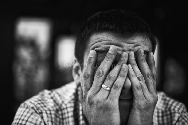 Trauriges und deprimiertes Bedeckungsgesicht des jungen Mannes - glaubendes deprimiertes Hintergrundkonzept - Heirat-Ausfall-Konz stockbild