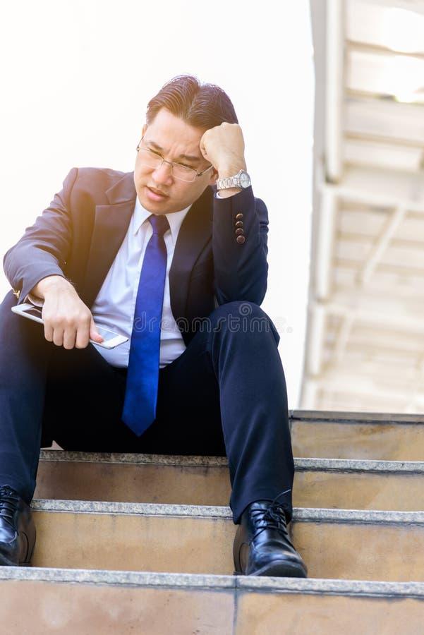 Trauriges und frustriertes Umkippenausfallung des asiatischen Geschäftsmanngefühls im Leben lizenzfreies stockbild