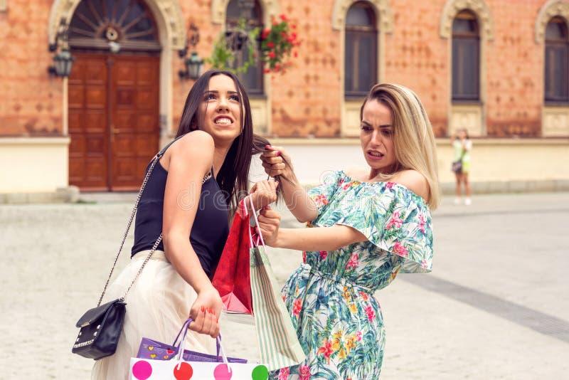 Trauriges und glückliches Mädchen, das am Einkaufen argumentiert stockfotografie