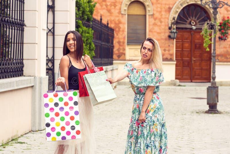 Trauriges und glückliches Mädchen am Einkaufen stockbild