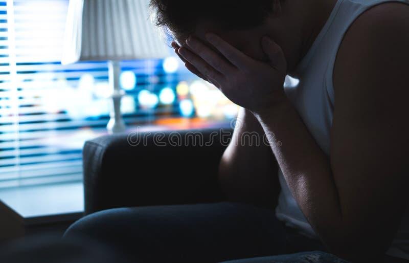 Trauriges und unglückliches Mannbedeckungsgesicht mit den Händen in der Dunkelheit durch Fenster stockfotos