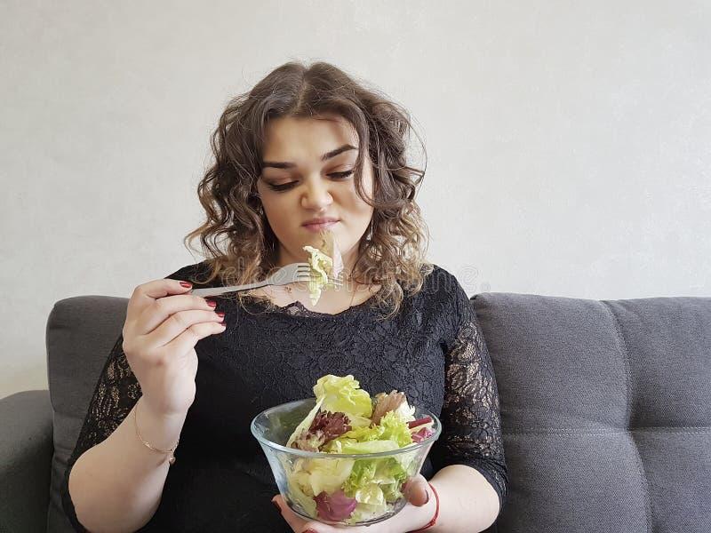 Trauriges volles schönes Mädchen auf Sofa mit Salat drückte die unglückliche Tellerdiät nieder lizenzfreies stockfoto