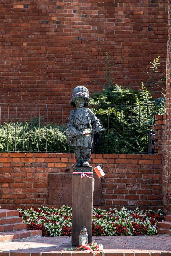 Trauriges Warschau-Monument eines kleinen Rebellen belichtet durch die Sommer warme August-Sonne vor dem hintergrund einer Backst lizenzfreie stockfotografie