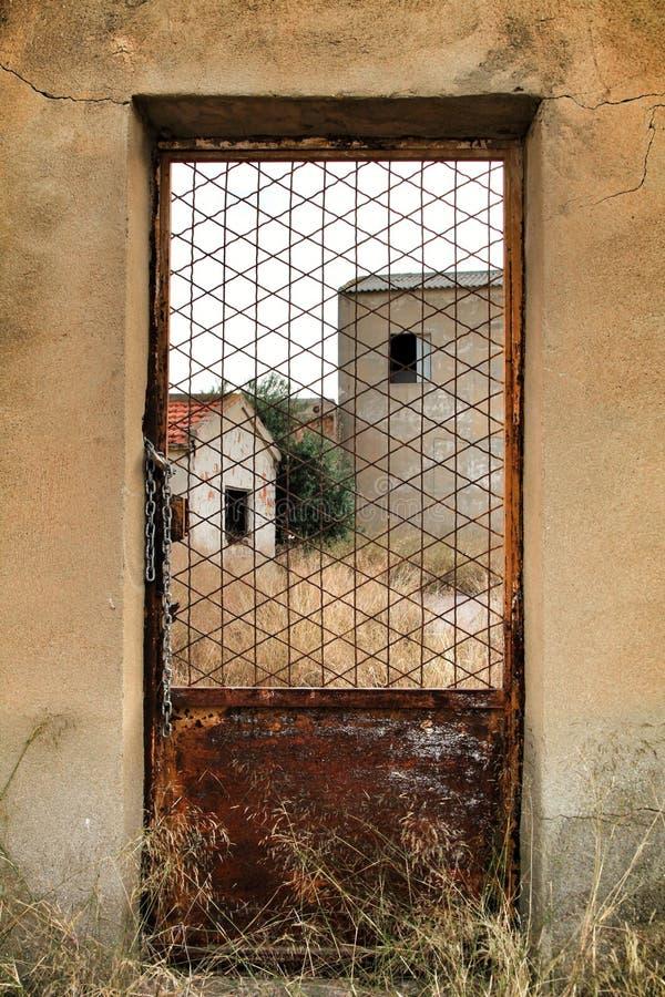 A través puerta oxidada vista fábrica abandonada vieja del metal imágenes de archivo libres de regalías