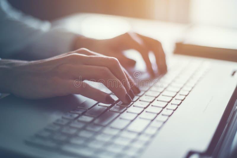 Travail à la maison avec la femme d'ordinateur portable écrivant un blog Mains femelles sur le clavier photographie stock libre de droits