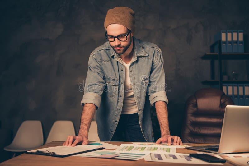 Travail au type de patron de nuit concentré lisant le contrat pour porter le support occasionnel d'équipement près de la table da photos libres de droits