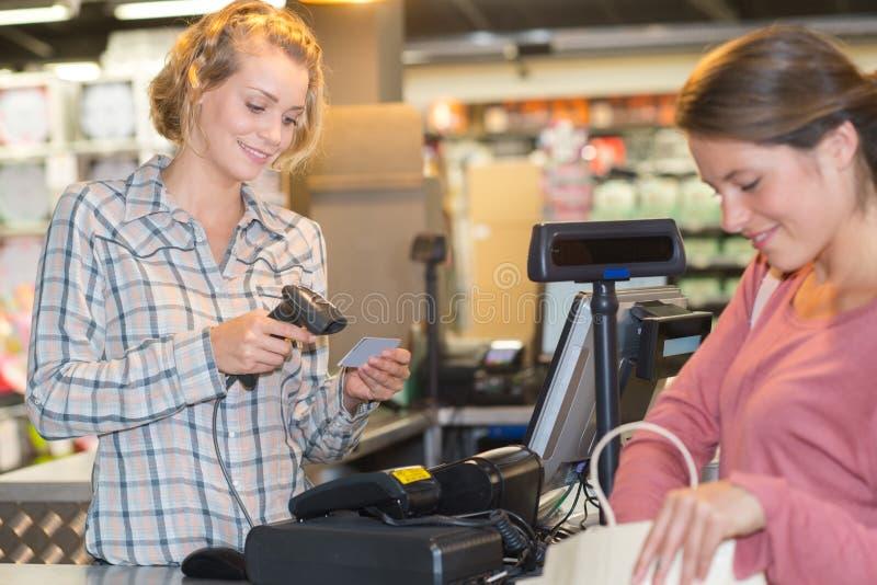 Travail auxiliaire de ventes au contrôle photographie stock