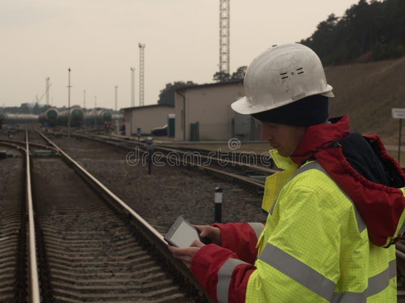 Travail coordonné de jeune ingénieur utilisant le comprimé moderne Employé ferroviaire dans l'ouest de sécurité et chemin de fer  image stock