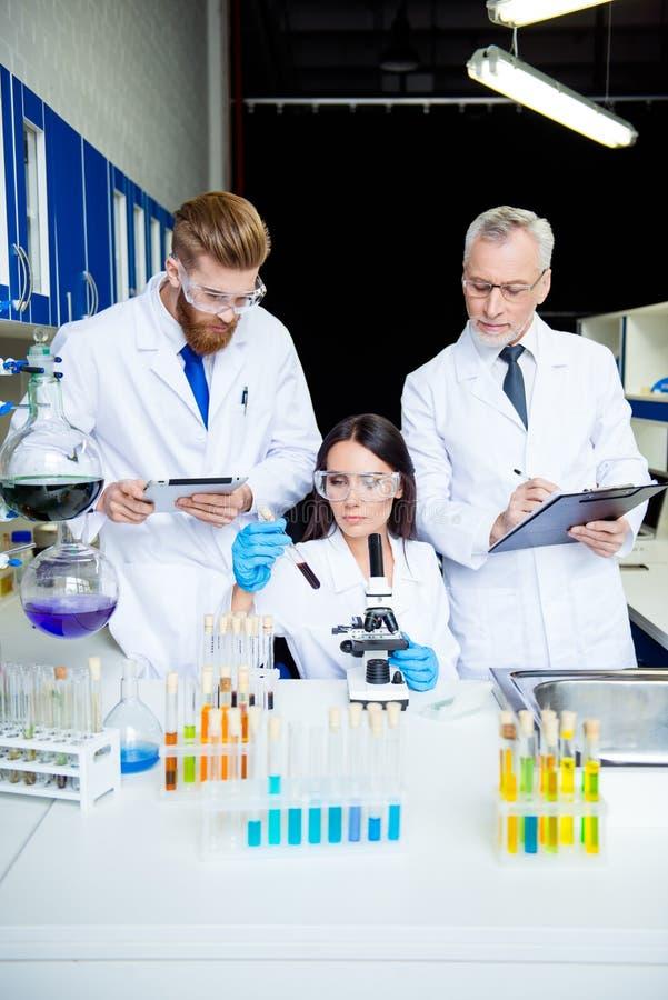 Travail d'équipe de trois Le groupe de scientifiques travaillent pour inventent t images stock