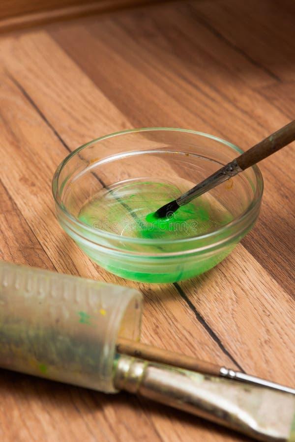 Travail d'aquarelle Brosse avec la peinture verte dans l'eau photographie stock