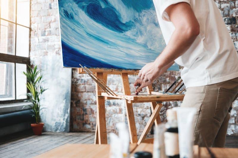 Travail d'artiste dans le studio d'art près du chevalet avec la toile Le peintre peint une peinture avec des peintures à l'huile  photos libres de droits