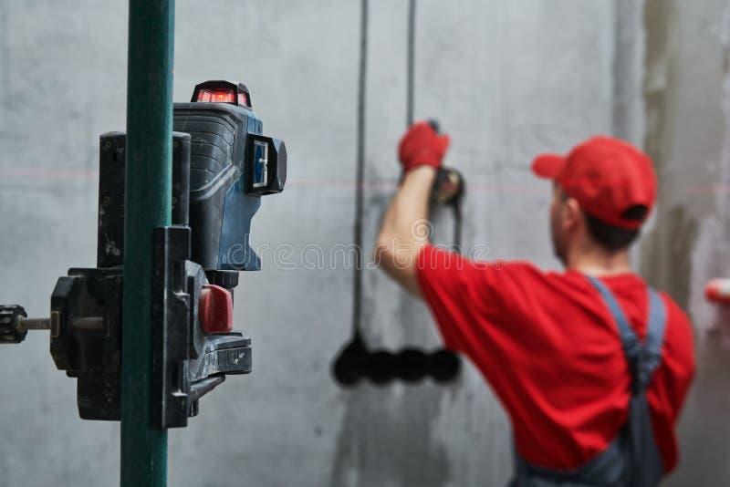 Travail d'Elecrician installation électrique de prise murale avec le niveau de laser photographie stock libre de droits