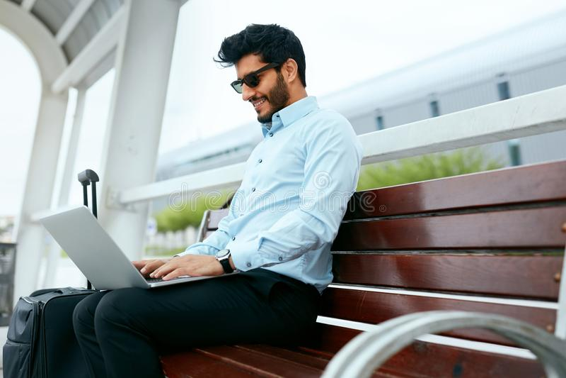 Travail d'homme d'affaires sur l'ordinateur portable dehors photos stock