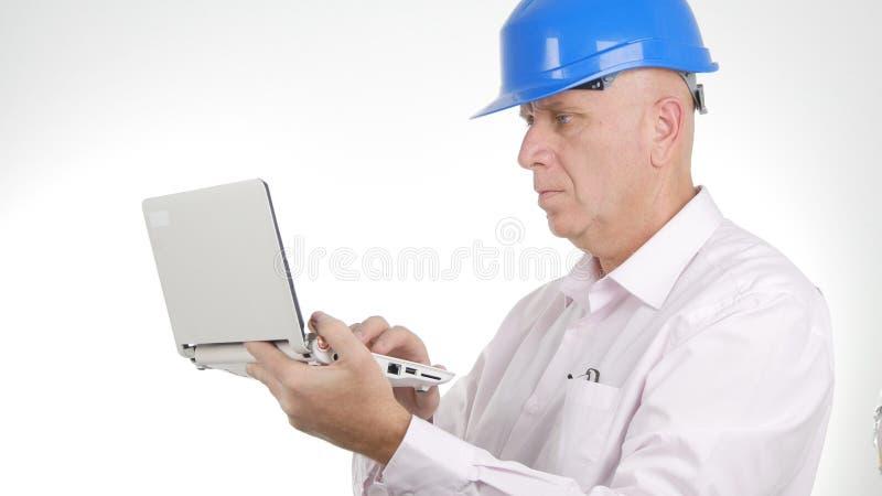 Travail d'Image Wearing Hardhat d'homme d'affaires utilisant la communication sans fil d'ordinateur portable photos libres de droits