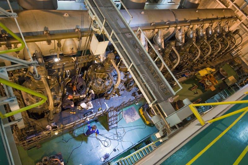 Travail d'ingénieurs sur un moteur marin énorme photographie stock libre de droits