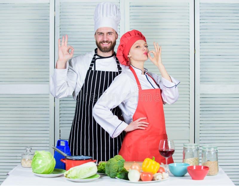 Travail d'?quipe dans la cuisine Accouplez faire cuire le d?ner Associ?es culinaires de femme et d'homme barbu D?ner d?licieux de photo stock
