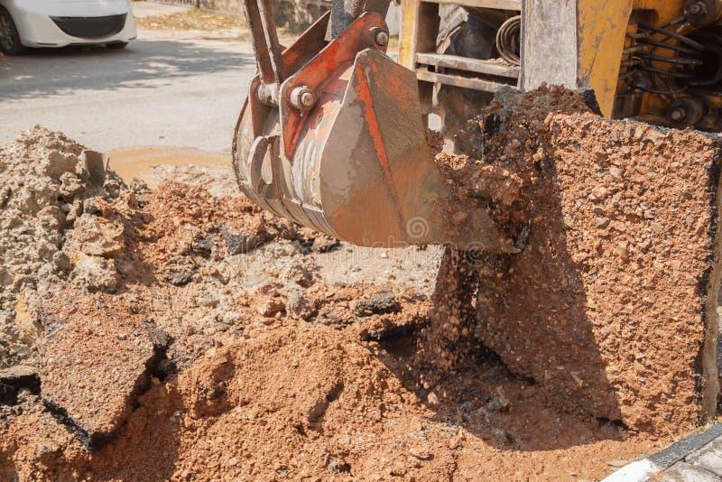 Travail de bouteur de seau d'excavatrice un trou la réparation du tuyau photographie stock
