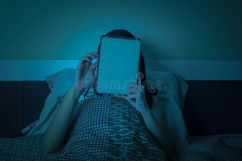 Travail de femme avec le comprimé ou l'ordinateur sur le lit la nuit photographie stock