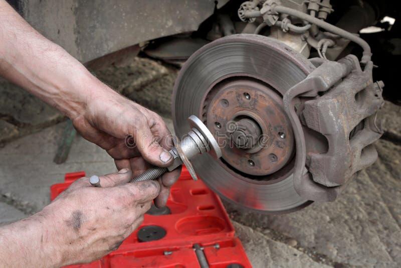 Travail de mécanicien de voiture sur des freins à disque images libres de droits