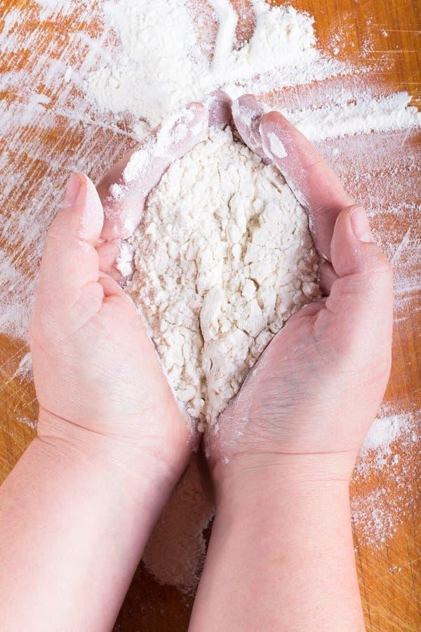 Travail de mains des femmes dodues avec de la farine sur une table en bois légère image libre de droits