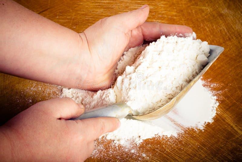 Travail de mains des femmes dodues avec de la farine sur une table en bois légère toned image stock