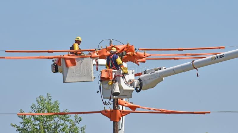 Travail de service de monteurs de lignes sur une ligne à haute tension images libres de droits