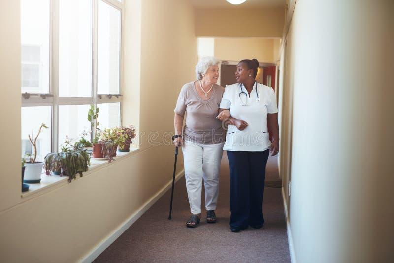 Travail de soins de santé aidant le patient féminin image libre de droits